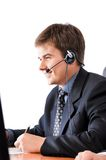 Customer service representative. Smiling male customer service representative with headset is isolated against white background Royalty Free Stock Images
