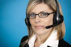 Customer service representative. A beautiful customer service representative with headset on a blue background Royalty Free Stock Photo