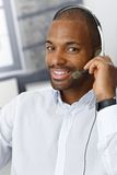 Customer service representative. Closeup portrait of smiling handsome Afro-American customer service representative working with headset Royalty Free Stock Images