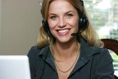 Customer Service representative. Working at the computer smiling at the camera Stock Photo