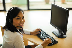 Customer Service Representative Alone Headset. A cute Asian customer service representative turns her head looking into the camera while working at a computer on Stock Photo