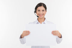 Customer service representative. Beautiful young female customer service representative in headset holding poster and looking at camera while isolated on white Royalty Free Stock Image