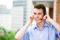 Customer service representative or call center agent or support or operator with headset on outside balcony Royalty Free Stock Image