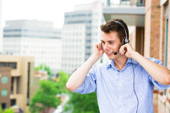 Customer service representative or call center agent or support or operator with headset on outside balcony Royalty Free Stock Photos