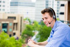 Customer service representative or call center agent or support or operator with headset on outside balcony Stock Images