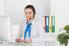 Customer service representative. Cheerful young female customer service representative in headset working at the computer and smiling Royalty Free Stock Image