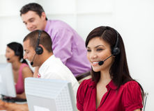 Customer service representative with headset on. Smiling Customer service representative with headset on in a call center Stock Photos