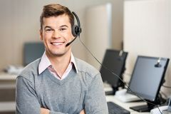Customer Service Representative With Headset In. Portrait of confident male customer service representative with headset in call center Stock Photo