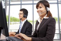 Customer service representative in modern office. Smiling customer service representative in modern office with a headset Royalty Free Stock Image