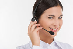 Customer service representative. Portrait of beautiful young female customer service representative in headset looking at camera and smiling while isolated on Stock Photography