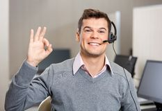 Customer Service Representative Showing Ok Sign. Portrait of young male customer service representative showing ok sign in office Royalty Free Stock Images