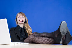 A customer service representative smiling during a telephone conversation. With her feet on the desk, shot against a blue chromakey background Stock Photo