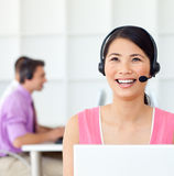 Customer service representative using headset. Laughing Customer service representative using headset in the office Royalty Free Stock Image