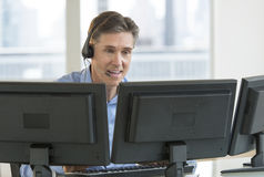 Customer Service Representative Using Multiple Screens. Happy mature male customer service representative using multiple screens at desk in office Stock Image