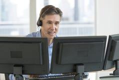 Customer Service Representative Using Multiple Screens. Happy mature male customer service representative using multiple screens at desk in office stock image