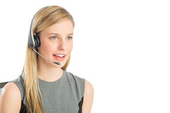 Customer Service Representative Wearing Headset Looking Away. Close-up of beautiful customer service representative wearing headset looking away against white Royalty Free Stock Images