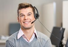 Customer Service Representative Wearing Headset. Portrait of confident male customer service representative wearing headset while smiling in office Royalty Free Stock Photo