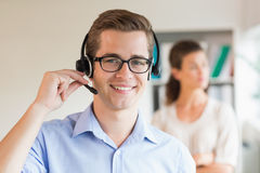 Customer service representative wearing headset. Portrait of young customer service representative wearing headset in office Royalty Free Stock Photo