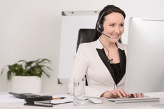 Customer service representative at work. Beautiful middle-aged c. Ustomer service representative typing something on computer and smiling Stock Image