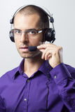 Customer Service Representative. Young man with headset in purple shirt Stock Images