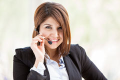Customer service with a smile. Happy Hispanic female call center representative wearing a suit and a headset and taking a customer service call Royalty Free Stock Images