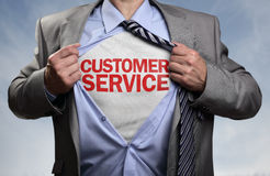 Customer service superhero. Businessman in classic superhero pose tearing his shirt open to reveal t shirt with customer service concept for assistance, contact stock image