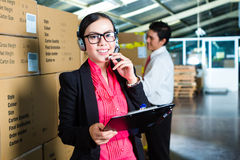 Customer Service in a warehouse. Young women in a suit with headset in a warehouse, she is from the Customer Service, a coworker standing in background Stock Photo