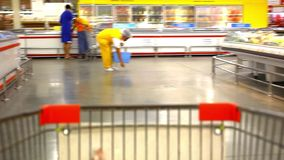 Customer shopping at supermarket with trolley and stock footage