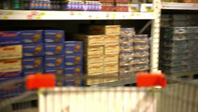 Customer shopping at supermarket with trolley stock video
