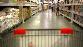 Customer shopping at supermarket with trolley. stock video footage