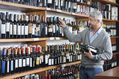 Customer Shopping For Wine Bottles In Store. Mature male customer shopping for wine bottles in store Royalty Free Stock Image