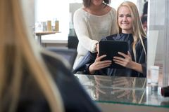 Customer Showing Hair Style on Digital Tablet Royalty Free Stock Image