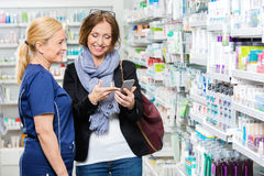 Customer Showing Mobile Phone To Pharmacist In Royalty Free Stock Photos