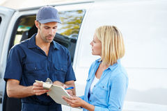 Customer Signing For Delivery From Courier Stock Images