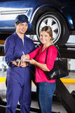 Customer Signing Document With Mechanic At Garage. Portrait of happy female customer signing document with mechanic in garage Stock Images