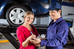 Customer Signing Document With Mechanic In Garage. Portrait of happy customer signing document while standing with mechanic in garage Royalty Free Stock Images