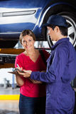 Customer Signing Document While Standing With Mechanic. Portrait of smiling female customer signing document while standing with mechanic in garage Royalty Free Stock Photography