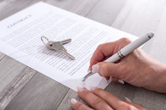 Customer signing a real estate contract. Female customer signing a real estate contract Stock Photo