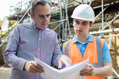 Customer On Site Discussing Plans With Builder. Customer On Site Discusses Plans With Builder Royalty Free Stock Photo
