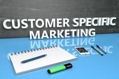 Customer Specific Marketing. Text concept with chalkboard, notebook, pens and mobile phone. 3D render illustration Stock Photos