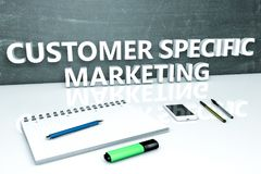 Customer Specific Marketing. Text concept with chalkboard, notebook, pens and mobile phone. 3D render illustration Royalty Free Stock Images