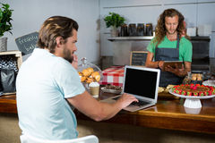 Customer and staff using laptop and digital tablet at counter Stock Photos