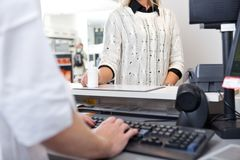 Customer Standing at Checkout Counter. Mid-section of customer standing at checkout counter in drugstore Stock Photography