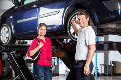 Customer Standing With Mechanic Filling Air In Tire Royalty Free Stock Photo