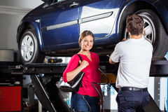 Customer Standing With Mechanic Refilling Tire. Portrait of smiling female customer standing with mechanic refilling tire at garage Stock Photography