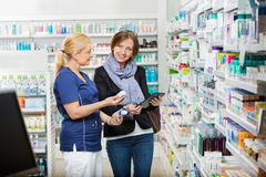 Customer Standing By Pharmacist Showing Medicines In Pharmacy royalty free stock photo