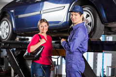 Customer Standing With Technician Filling Air In Royalty Free Stock Photo