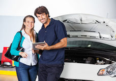 Customer Standing With Technician Holding Digital Tablet. Portrait of happy female customer standing with technician holding digital tablet by car in garage Royalty Free Stock Image