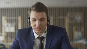 Customer support agent with headphones and microphone in modern office