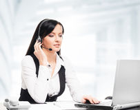 Customer support operator working in a call center office. Young brunette customer support operator working in a call center office Stock Photo